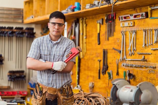 El técnico se para en la sala de herramientas, sosteniendo una llave.