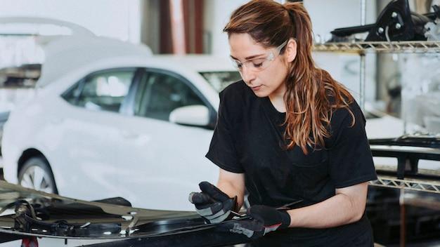 Técnico de sexo femenino que fija las piezas del coche en un garaje