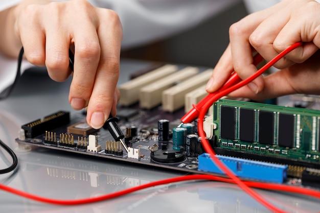 Técnico de sexo femenino que repara la placa base del ordenador