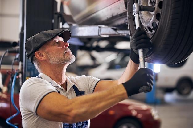 Técnico de sexo masculino guapo que repara la rueda del coche en la estación de servicio