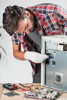 Técnico de sexo masculino joven que examina la computadora en taller