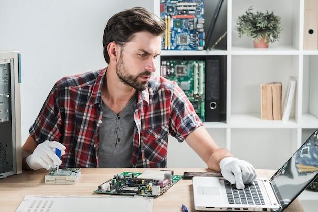 Técnico de sexo masculino que mira el ordenador portátil mientras que repara la computadora