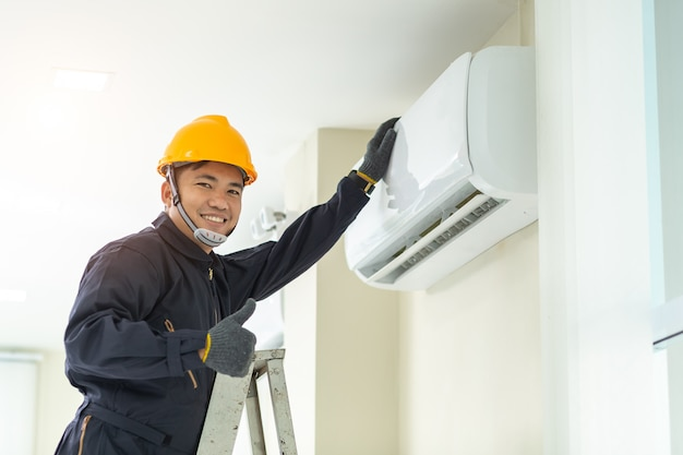 Técnico de sexo masculino que repara el uniforme de seguridad del aire acondicionado dentro.