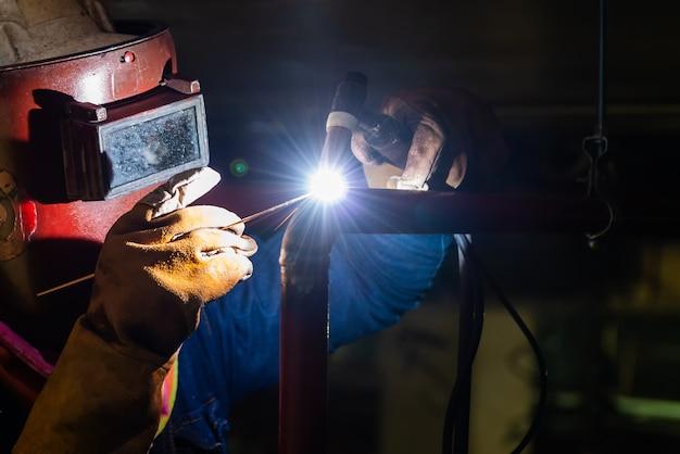 Técnico soldador de acero con gas en el área de fabricación.