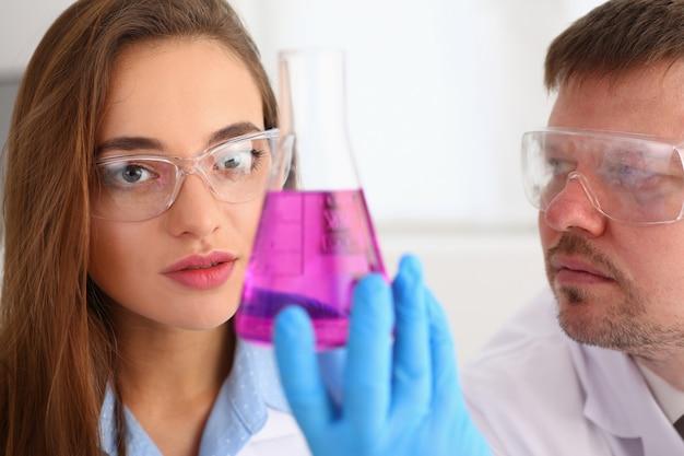 Técnico sostenga en brazos en guantes protectores botella de muestra