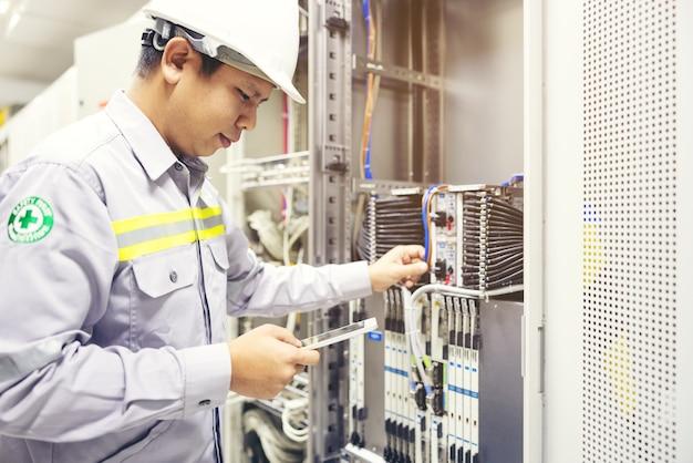 Técnico con tableta digital en la sala de servidores, reparación de la placa base de la tarjeta comprobando el estado del enlace de red
