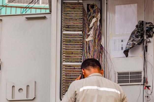 Técnico telefónico comprueba el cable coaxial.
