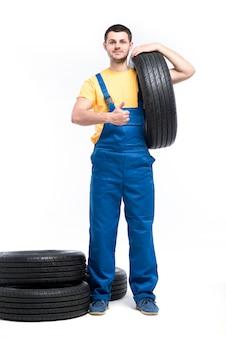 El técnico en uniforme azul sostiene el neumático en la mano, fondo blanco, reparador con neumáticos