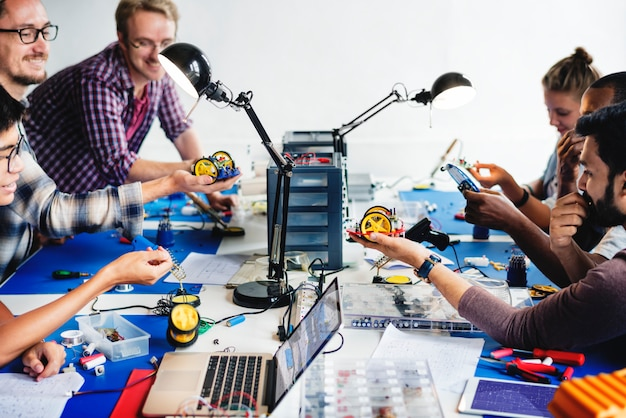 Técnicos eléctricos trabajando en piezas de robot.