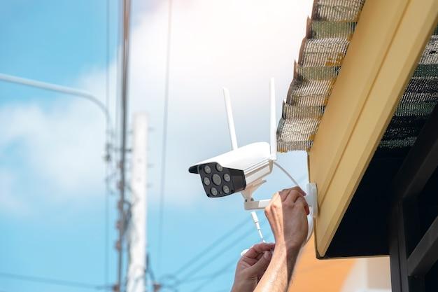 Los técnicos están instalando una cámara cctv inalámbrica en el frente de la casa para mantener la seguridad.