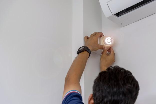 Los técnicos están instalando una cámara de cctv en la pared.
