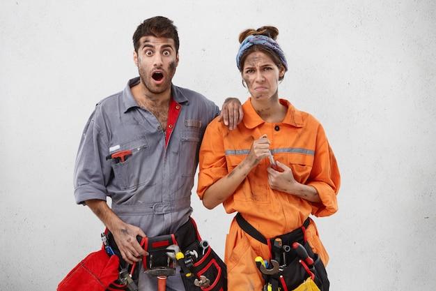 Técnicos masculinos y femeninos asombrados y disgustados ven que hay fugas de agua en la cocina
