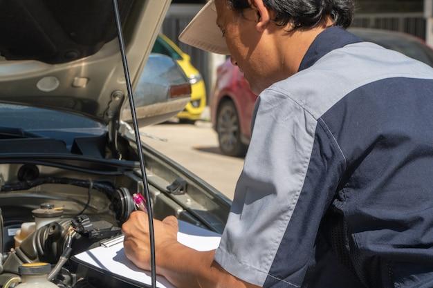Los técnicos profesionales de reparación de automóviles inspeccionan el motor de acuerdo con los documentos de la lista de verificación para garantizar