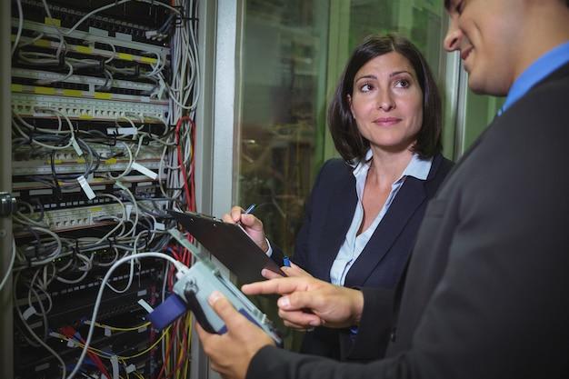 Técnicos que interactúan entre sí mientras analizan el servidor