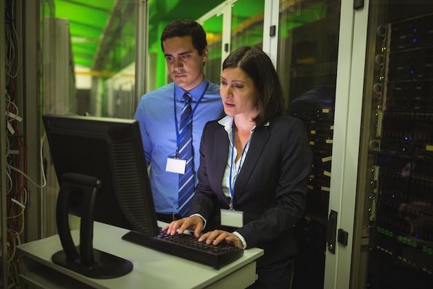 Técnicos que trabajan en la computadora personal mientras analizan el servidor