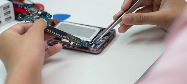 Técnicos para reparar teléfonos móviles.