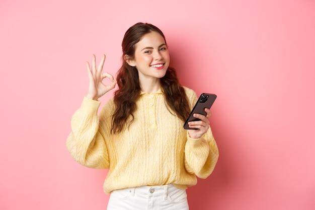 Tecnología y compras online. el modelo de mujer joven muestra un signo correcto y usa la aplicación de teléfono móvil, elogia la buena tienda, dice que sí, se para contra la pared rosada.