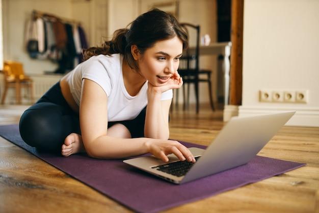 Tecnología, comunicación, aprendizaje a distancia y distanciamiento social. linda chica de talla grande con conexión inalámbrica a internet de alta velocidad en una computadora portátil, viendo el curso de instructor de yoga en línea, sentado en la alfombra