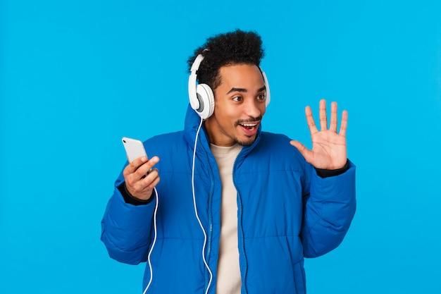 Tecnología, concepto de chat. elegante y atractivo joven estudiante afroamericano en chaqueta de invierno acolchada, escuchando música en camino a la universidad, sostenga los auriculares del teléfono inteligente, saludando, hola