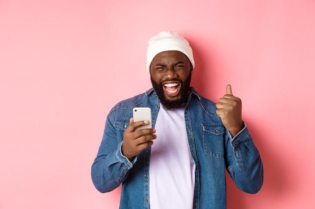 Tecnología y concepto de compras online. feliz hombre negro regocijándose, ganando en la aplicación, sosteniendo el teléfono inteligente y gritando que sí, de pie sobre fondo rosa