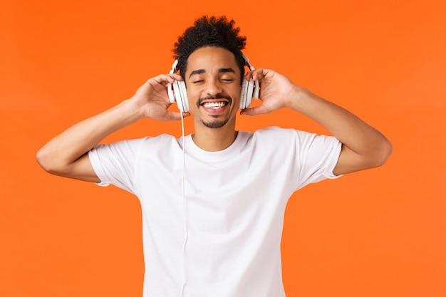 Tecnología, concepto de gadgets. feliz hombre afroamericano moderno en camiseta blanca ponerse auriculares