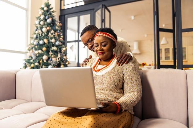Tecnología digital. buen hombre positivo de pie detrás de su esposa mientras mira a la pantalla del portátil