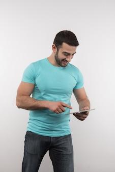 Tecnología digital. hombre alegre de pie contra el fondo blanco mientras usa una tableta