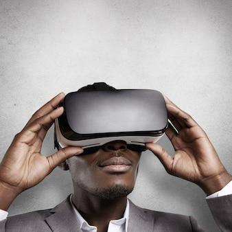 Tecnología y entretenimiento. oficinista africano con ropa formal, experimentando la realidad virtual, usando gafas de realidad virtual.