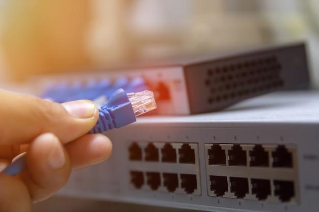 Tecnología de la información red de computadoras, cables ethernet de telecomunicaciones conectados a un conmutador de internet.