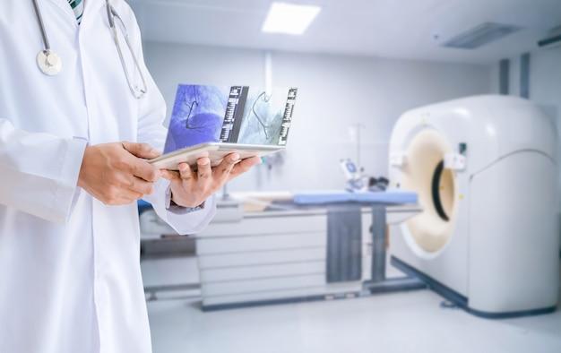 Tecnología del médico vea los resultados de las imágenes de resonancia magnética por resonancia magnética con una tableta