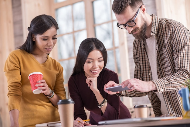 Tecnología moderna. agradable agradable hombre barbudo sosteniendo su teléfono inteligente y tomando una foto mientras está de pie junto con sus colegas alrededor de la mesa