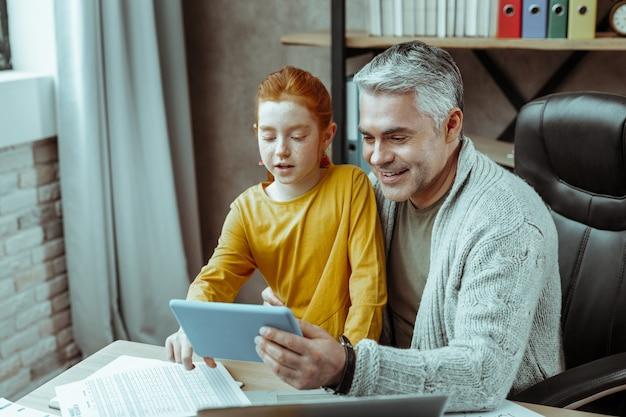 Tecnología moderna. hombre alegre positivo mirando la pantalla de la tableta mientras se la muestra a su hija
