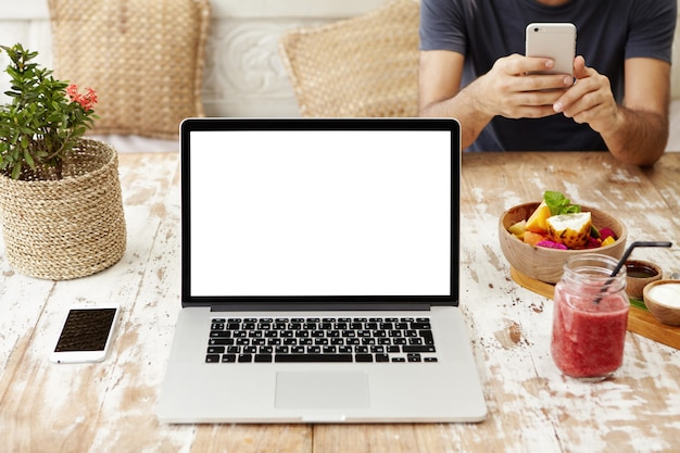 Tecnología, negocios, comunicación, personas y publicidad. vista frontal del lugar de trabajo de diseño de madera con portátil abierto con pantalla en blanco, teléfono celular, vaso de batido y tazón de frutas.