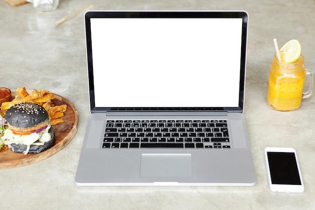Tecnología, negocios y procesos de trabajo. vista frontal del espacio de trabajo del profesional independiente: computadora portátil abierta con espacio de copia para su diseño, descansando sobre la mesa con teléfono inteligente