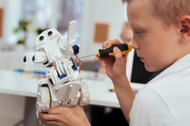Tecnología profesional. chico rubio inteligente construye un robot mientras está interesado en la tecnología