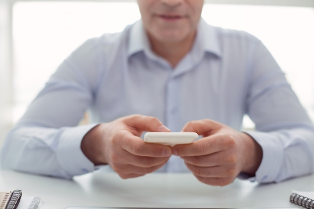 Tecnología profesional. enfoque selectivo de un teléfono inteligente moderno en manos de un hombre guapo agradable mientras está sentado en la mesa