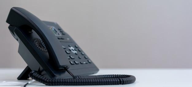 Tecnología voip telefónica de pie en el escritorio de la oficina en la sala de oficina para contacto