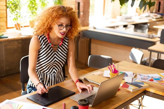 Tecnologías en acción. gerente creativo con gafas utilizando tecnologías modernas en el trabajo