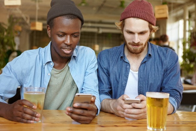 Tecnologías, comunicación en línea y adicción a internet. apuesto chico caucásico con barba y su amigo o compañero afroamericano disfrutando de una cerveza fresca en un pub y navegando por las redes sociales en los móviles