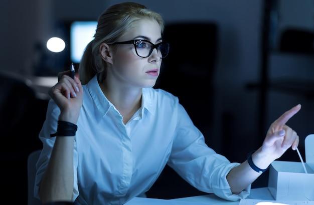 Tecnologías digitales en mi uso. hacker hábil concentrado involucrado sentado en la oficina y decodificando información mientras ingresaba al sistema informático de la empresa