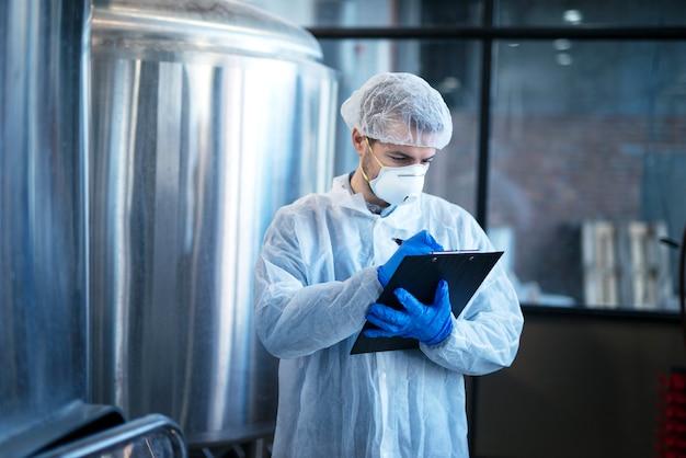 Tecnólogo concentrado experto en traje blanco controlando la producción en fábrica de alimentos