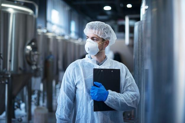 Tecnólogo en traje blanco protector con redecilla y máscara de pie en la fábrica de alimentos