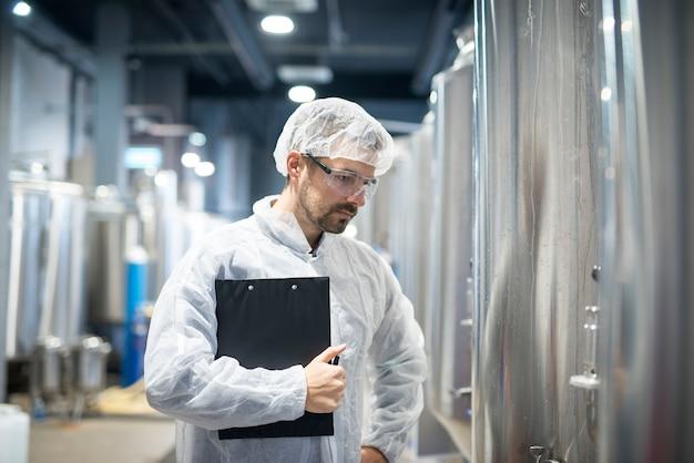 Tecnólogo en uniforme protector blanco de pie en la planta de la industria