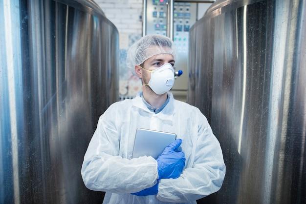 Tecnólogo en uniforme protector con tableta de pie junto al depósito de metal en la industria de procesamiento de alimentos