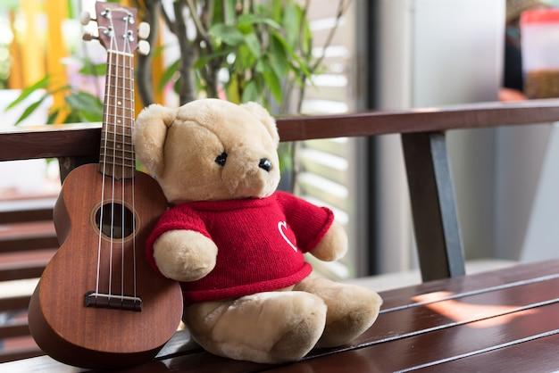 Teddy bear con ukulele en el balcón en el horario de verano.