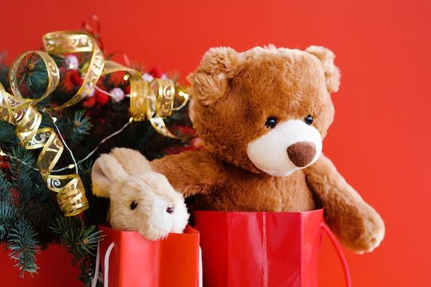 Teddy y conejito en bolsas de regalo rojo bajo el árbol de navidad.