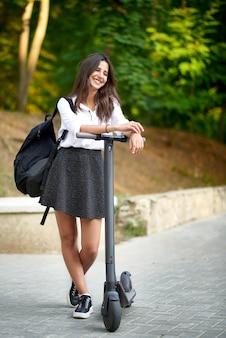 Teen high school girl sonriendo y montando scooter eléctrico en el parque