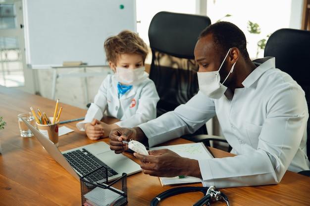 Teenboy caucásico como médico consultando, dando recomendaciones, tratando. pequeño doctor durante la discusión, estudiando con un colega mayor. concepto de infancia, emociones humanas, salud, medicina.