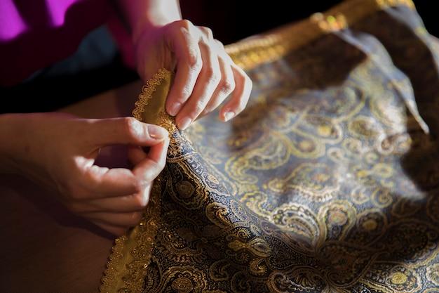 Tejer cinta dorada al tejido.