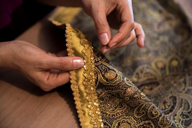 Tejer cinta dorada a la alfombra.